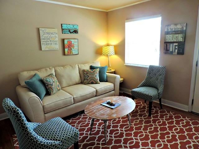 světlá pohovka, barevné židle, červený koberec