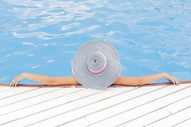 žena v klobouku u bazénu